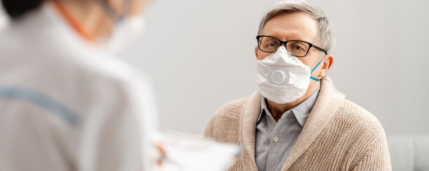 An elderly man wearing a face covering looking at a care worker